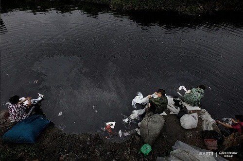 Women wash plastic cloth in polluted water